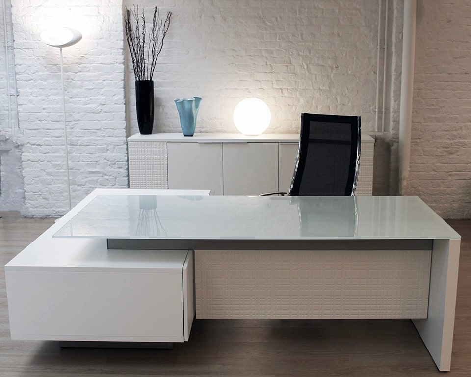 Modi White glass L shaped Executive desks with a white glass desk top and white lacquered lowered side return with drawers and storage. , black glass or real wood tops are also available. Shown here with a matching white lacquered credenza and a black mesh luxury high back executive chair