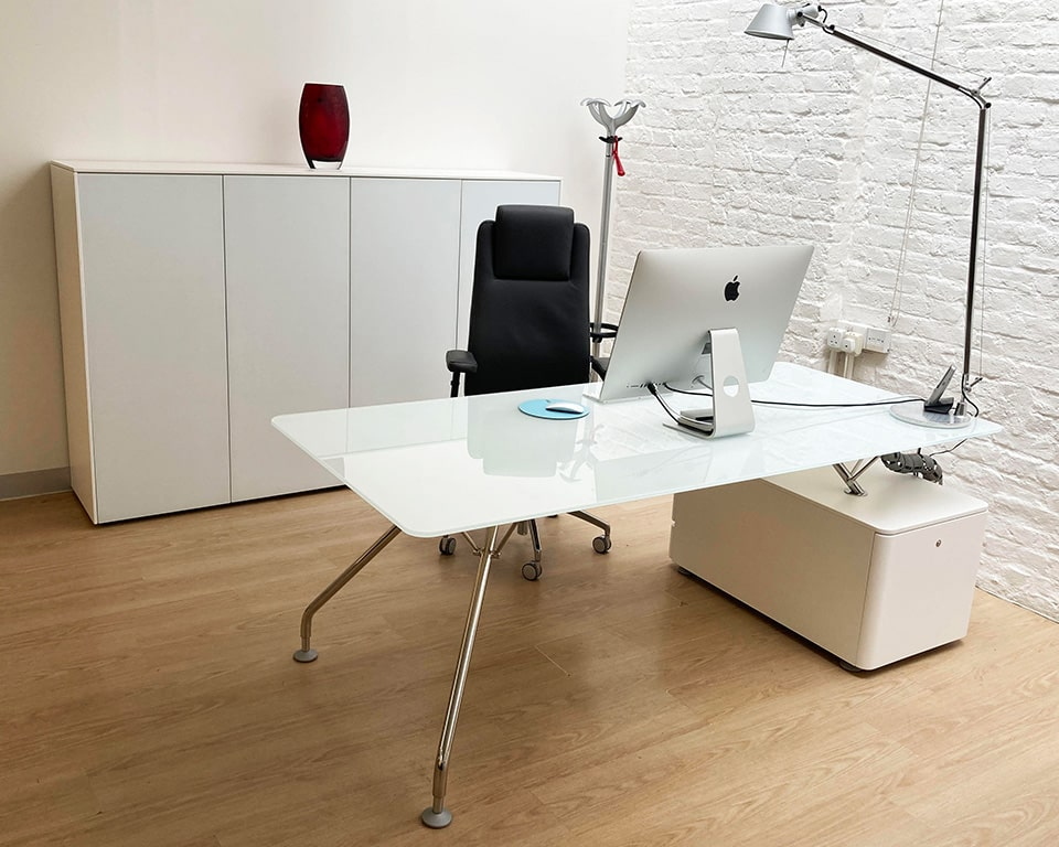 Prospero White glass designer desks for executives or home offices with white glass desk tops and matt white lacquered structural storage and chrome legs. shown here with matching round glass table and a high back leather executive chair with height adjustable arms