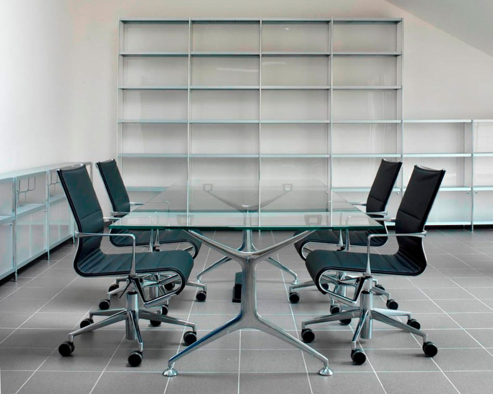 frame-large clear glass boardroom table with die cast aluminium legs with black leather rolling frame chairs