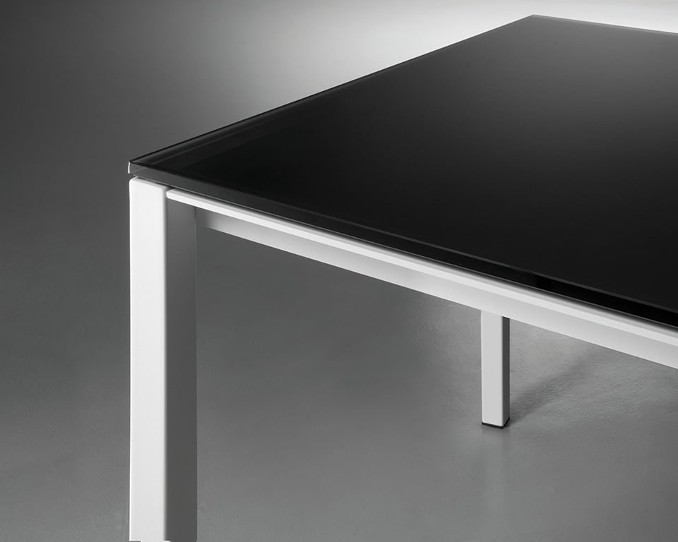 Detail of the black satin glass desk top with white legs