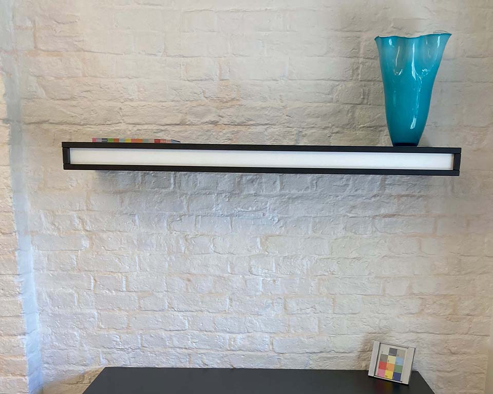 On and Friday Wall mounted 1270 wide wall mounted thick shelf in black and white lacquered with blue vase display