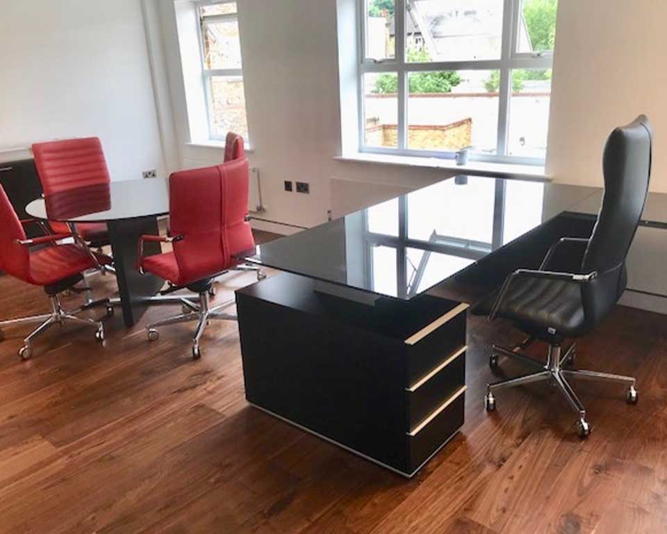 Luxury Modi office furniture in black glass with a round black glass table and four red leather tempo meeting room chairs. Black glass L shaped executive desk with a high back black leather executive chair