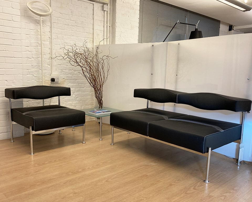 High quality Italian office reception sofas , armchairs and matching acid etched glass coffee tables. Shown here with a chrome frame and black Italian leather upholstery with white stitching detail