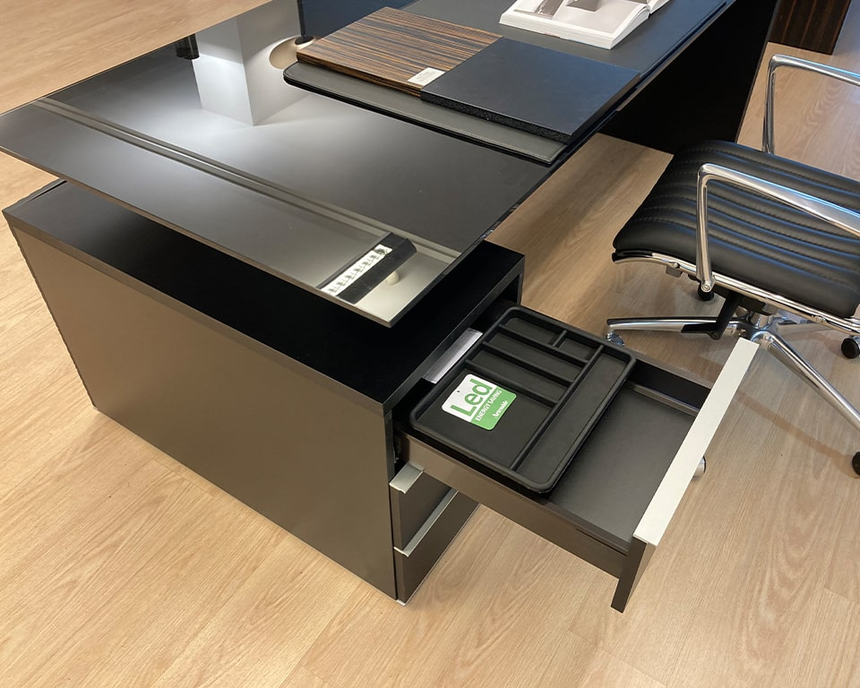 High - end Modi black glass executive desk detail of the black lacquered top drawer when open showing the pen tray