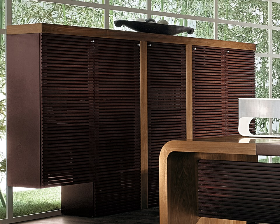 TAU luxury high storage cupboard in Italian walnut with the dark wood strips design on the glass doors . Shown with the matching Tau high - end CEO executive desk