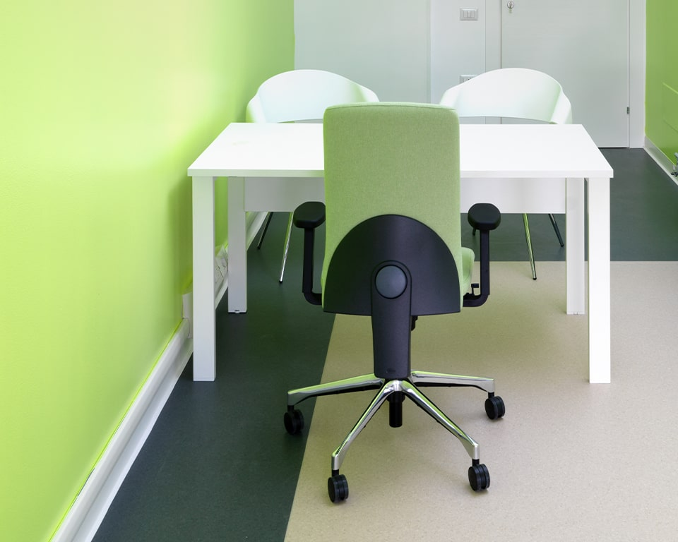 ECLIPSE task chair in green fabric - rear view showing the height adjustable back detail and die cast polished aluminium base. Also with a white desk and 2 white lacquered Chantal visitors chairs