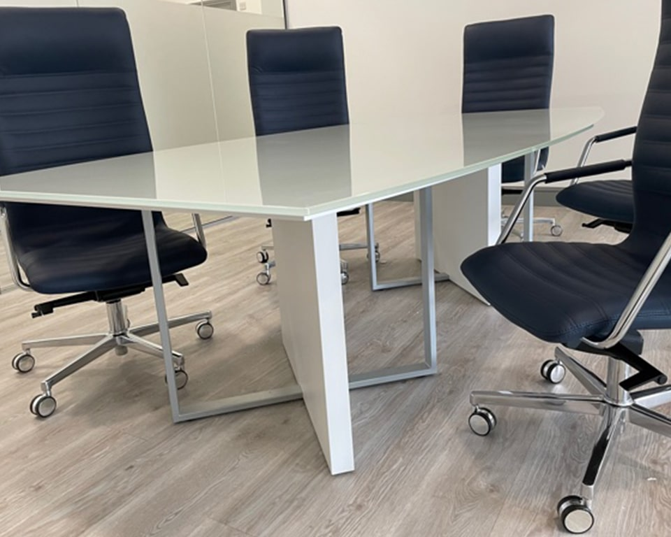 Close up detail of the Modi meeting table leg in matt white lacquered. The special white glass boat shaped top is very stylish and enhanced further with dark blue leather high quality Tempo boardroom chairs