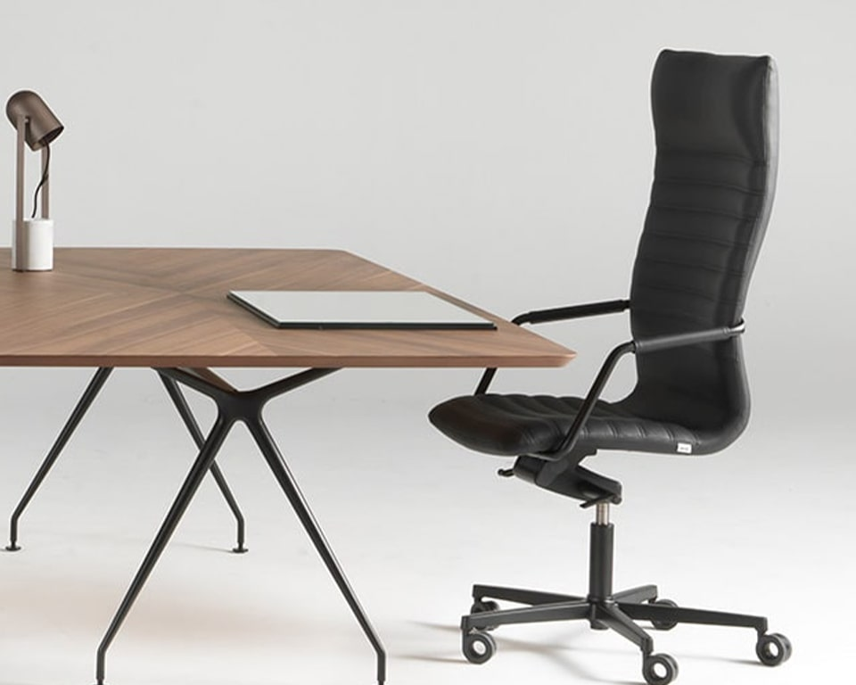 Tempo High back executive office chairs are high quality Italian executive chairs in real leather of fabric upholstery. Shown here with a black 5 star base and castors seated behind a Canaletto walnut Dapper executive table