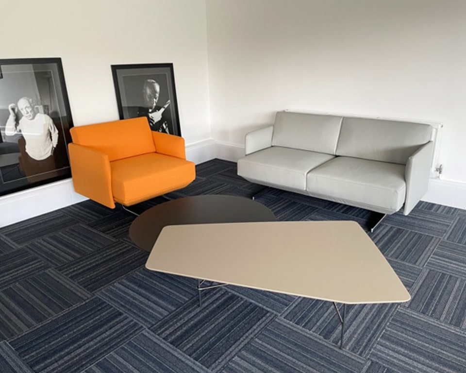 High quality Italian armchairs and sofas - Shown here in orange fabric and grey leather with die cast aluminium frame. In the foreground is the stylish lovers twin height large coffee table with a chrome frame