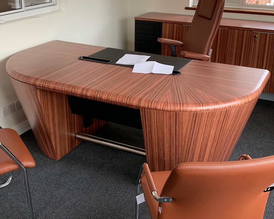 Luxury High - end executive office desk in zebra wood shown with a BOW high quality fully adjustable executive chair with headrest and upholstered arms. Matching tempo visitors chairs in Tan leather. Premium quality executive office furniture with wire management and an exquisite grain pattern