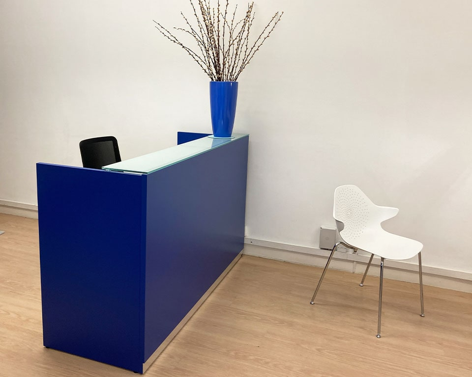 Small high quality reception desks- BG Small reception desks are part of the larger modular range of Italian designer desks for office reception areas and break out seating areas. These stylish desks shown here in matt blue lacquer are available in 4 sizes 1800 mm wide, 1600mm , 1400 mm and 1200 x 630 x 1080mm high. They all have a laminated glass counter top. The desk top includes 2 cable ports for cable egress onto the desk surface. An excellent compact reception desk for small or large office reception areas.