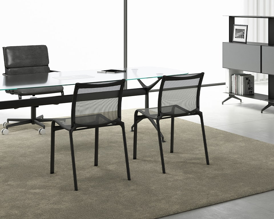 Black mesh dining chairs - high quality Italian side chairs suitable for dining or office meeting areas . Shown here in black with a a Frame table used as an executive desk with matching black structure and a transparent glass top