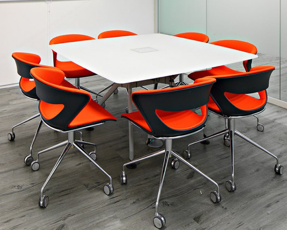 Modern meeting room chairs with ergonomic designer comfort levels on a 4 spoke swivel base. Fully upholstered in red fabric with a black outer shell. 4 spoke swivel base in chrome with castors
