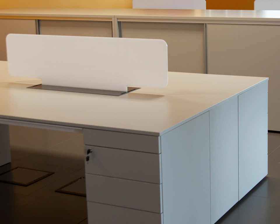 Detail of the perspex screen divider for High quality Minimum double desks and benches showing the lockable 5 drawer structural pedestals