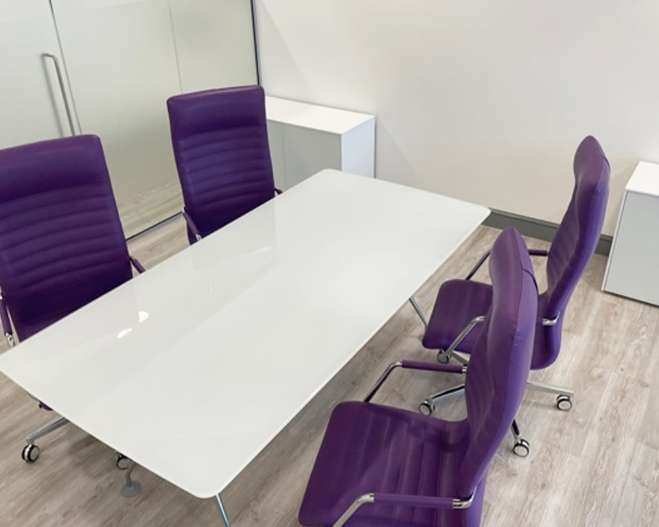 White glass meeting table with high back tempo boardroom chairs in purple