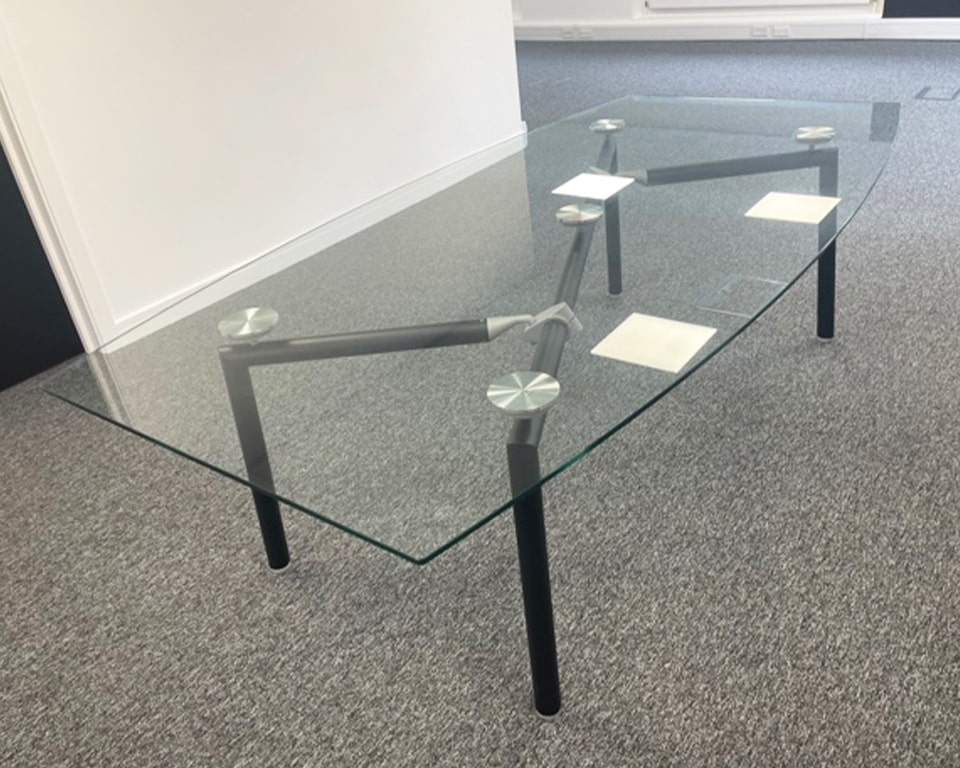 Glass boardroom table to seat 10 with black legs boat shaped clear glass table top