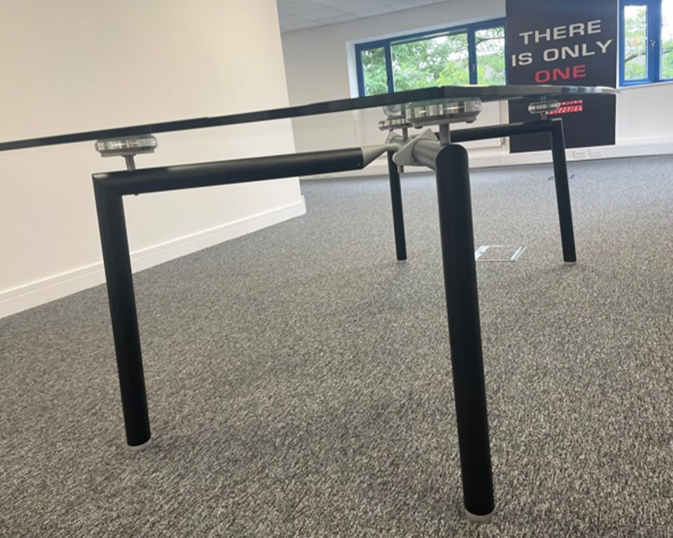 Glass boardroom table with black legs boat shaped clear glass table top