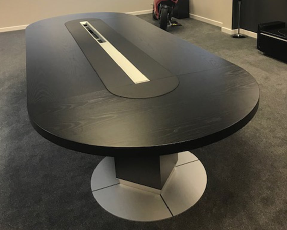 Taiko Large Boardroom table in black ash with a black leather central inlaid section. Within the centre of the inlaid section are lift up lids to reveal a horizontal cable channel