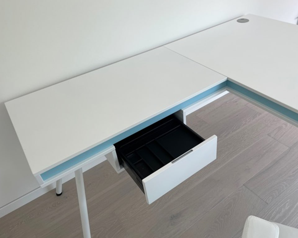 Large White L- shaped desk with sky blue detailing. Cable managed desk with a single shallow drawer.White Legs