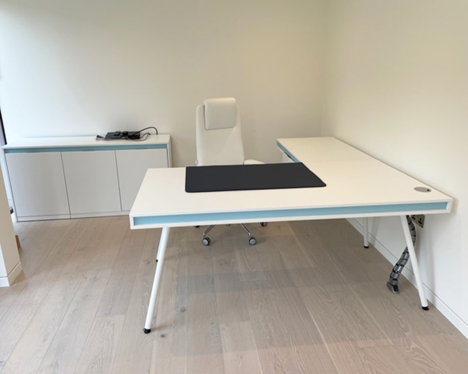 Large White L- shaped desk with sky blue detailing. Cable managed desk with a single shallow drawer.White Legs and matching low sideboard