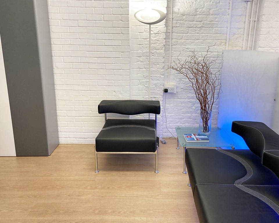 Cabildo Floor standing Italian uplighter in reception area setting with black leather reception area seating